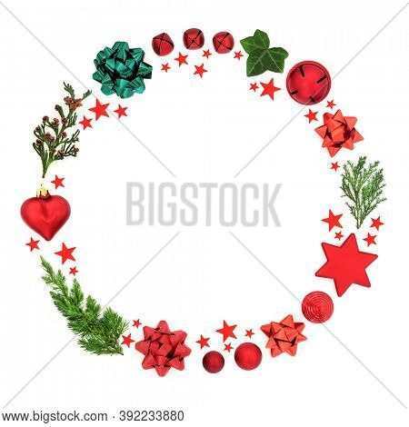 Abstract Christmas wreath decoration with cedar, fir & ivy leaves with baubles, bows & red stars on white background. Festive composition for the holiday season. Flat lay, top view, copy space.