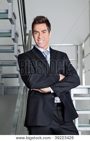 Portrait of confident happy young businessman standing on stairs