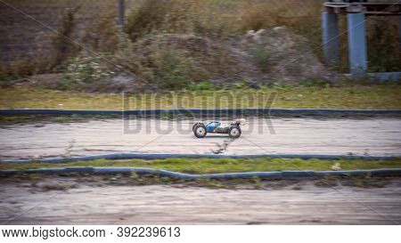 Blue And White Buggyr Going Very Fast On An Rc Offroad Track