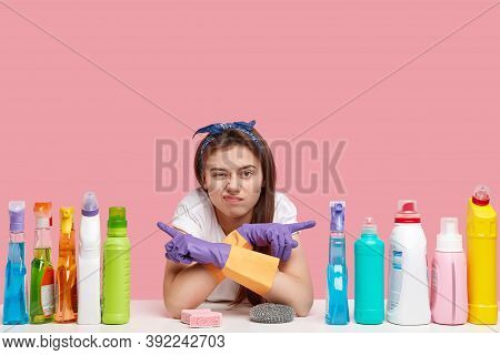 Indoor Shot Of Displeased Woman Points At Different Sides, Shows Cleaning Supplies, Doesnt Like Effe