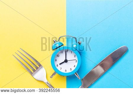 Blue Alarm Clock, Fork, Knife On Colored Paper Background. Intermittent Fasting Concept - Image