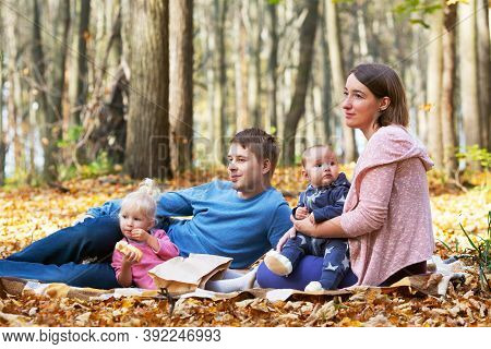 Family With Two Kids Spending Time In Autumn Park. They Are Sitting On Plaid And Eating Snacks. Weat