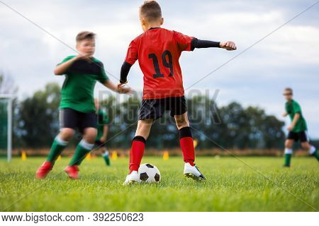 Children Playing Sports Soccer Match. Young Boys Compete In Football Tournament. School Boys Kicking