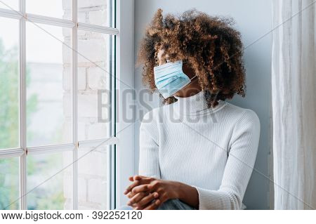 A Brooding African-american Girl With A Lush Hairstyle And A Medical Mask Sits On The Windowsill And