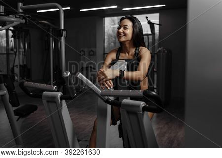 Happy Fitness Woman Resting After Training In The Gym. Mirror View Of Young Sporty Girl Laughing Dur