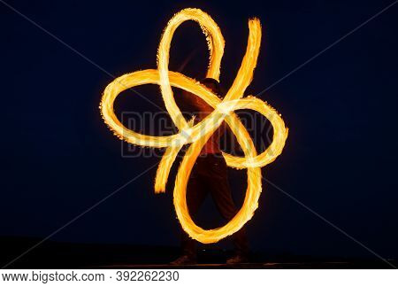 Solo Fire Artist Perform Infinite Spirals By Spinning Flaming Pois On Dark Sky At Night Outdoors, Bl