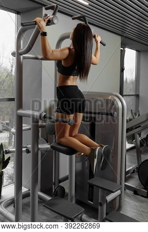 Strong Fitness Sport Woman Doing Pull-ups In A Gym For A Back Workout. Sexy Athletic Sport Woman Wit
