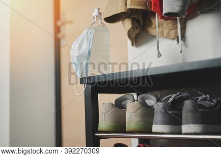 Sanitizer With Mask On Shoe Rack In Entrance Door Background