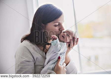A Newborn Baby In A Tender Embrace Of Mother At Window