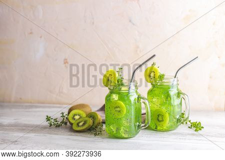 Two Glass Jar Of Kiwi Juice Or Smoothie. Kiwi Mojito Cocktail Or Non-alcohol Mocktail With Mint And