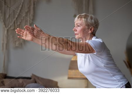 Senior Caucasian Woman Practicing Advanced Yoga Chair Pose Or Utkatasana