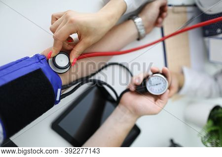 Cardiologist With Red Stethoscope Measures Blood Pressure Of Patient In Clinic Closeup. Diagnosis Of