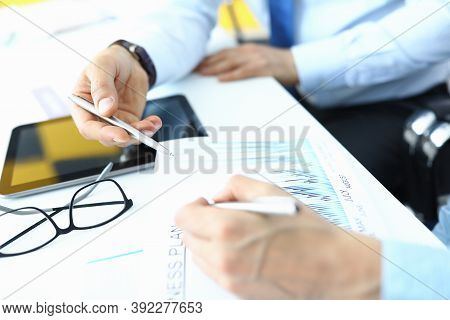 Male And Female Hands With Ballpoint Pens Over Document With Plan And Tablet At Table In Office Clos