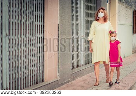 Woman and daughter wearing facial disposable mask to avoid viral infection. Coronavirus protection