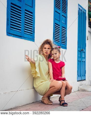 Mother and daughter next to shutter window in a street
