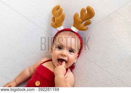 Cute Newborn Baby In Christmas Deer Costume. Happy Baby On A White Background. Closeup Portrait Of N