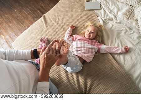 Mom Tickles Her Little Daughters Feet. The Girl Laughs Merrily.