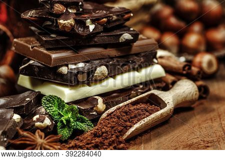 Stack Of Chocolate Slices With Mint Leaf On A Wooden Table.assortment Of Fine Chocolates In White, D