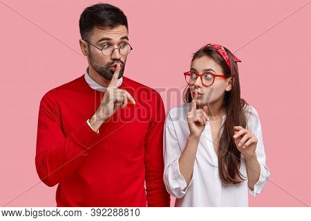 Photo Of Surprised Female And Male Gossip Together, Make Silence Gesture, Tell Secret Information, L