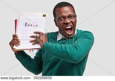 Irritated Dark Skinned Man Screams From Anger, Holds Paper Documents, Exclaims Loudly, Feels Depress