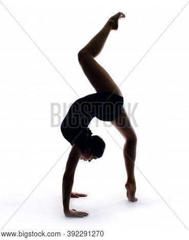 Graceful Female Gymnast In Sportswear Performs A Handstand. Training, Element Of Gymnastics, Acrobat