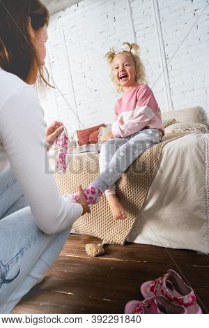 Mom Takes Off Her Little Daughters Socks And Tickles Her Feet A Little. The Girl Laughs.