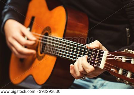 Hands Of Man Playing Guitar. Guitarist Holding An Acoustic Guitar. Handsome Man Playing Guitar At Th