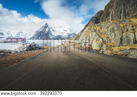 road with snow mountains and fisherman village background, spring time, Reine, Lofoten, Norway