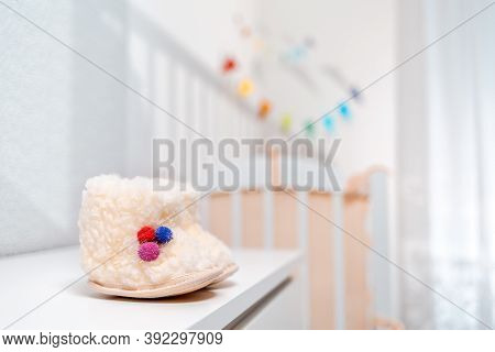 A Pair Of White Wool Baby Booties Are On The Dresser. Baby Crib On The Background. Nobody