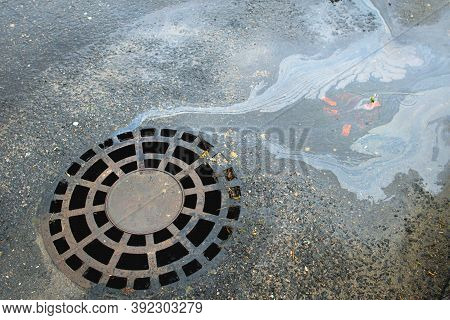 Oil Slick On The Asphalt Road Background Drains Into The Storm Drain