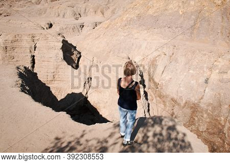 Woman Standing At The Edge Of A Precipice. The Deep Ravines Are Formed By Spring Streams That Erodes