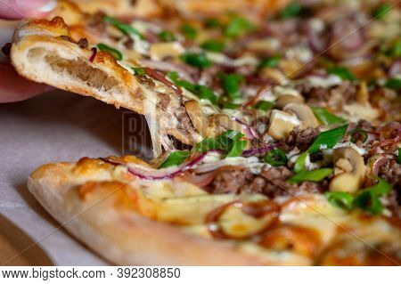 Close-up Of A Hand Breaks Off A Slice Of Pizza. Pizza With Mushrooms, Onions And Cheese.