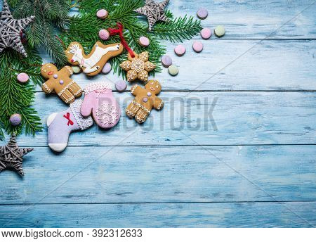 Blue wooden background with christmas decoration and ginger cookies. Christmas or New Year holiday background.  Top view.