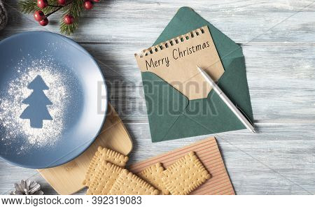 Famale Hand Writing A Christmas Letter On Wooden Background