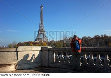 Male tourist taking photo of Eiffel Tower from observation deck on Bir-Hakeim bridge, Shadow of man on stone fence, Fall season sunny day blue sky real moment unfiltered photo