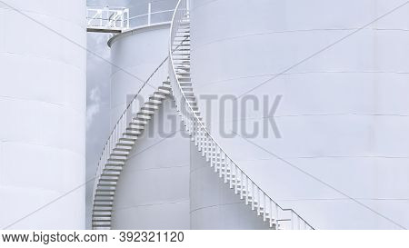 Part Of Curve Spiral Staircase On White Storage Fuel Tanks