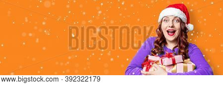 Cheerful Caucasian Santa Hat Woman Holding Gift Boxes With Red Bow Over Holiday Background