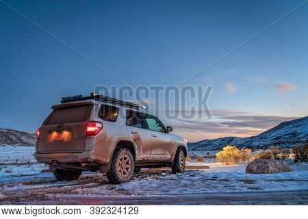 Fort Collins, CO, USA - October 28, 2020: Dirty Toyota 4runner SUV at dusk in Red Mountain Open Space , recreational area at foothills of Rocky Mountains in northern Colorado, fall scenery with snow.