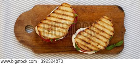 Tasty Grilled Caprese Panini (mozzarella, Tomatoes And Basil) On A Rustic Wooden Board, Top View. Fl