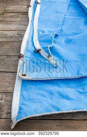 A Blue Jib Sail Rolled Up On The Dock With Shows A Close Up Of The Bolt Rope And Copper Hanks Sewn O