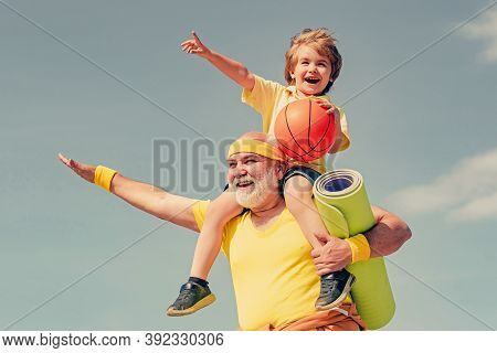 Like Sports. Joyful Old-aged Man And Cute Little Boy Practicing Sport And Healthy Lifestyle Over Sky