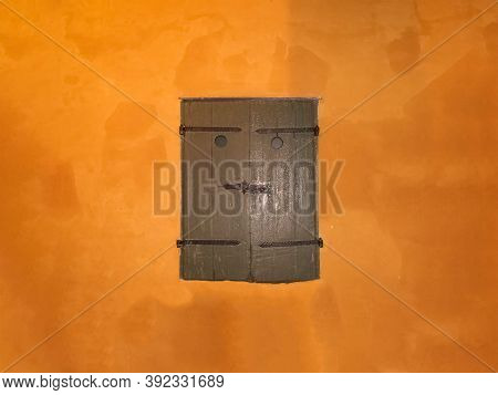 Gray Old Shutters On An Orange Painted Wall. Old Wooden Window Shutters Of European House With Orang