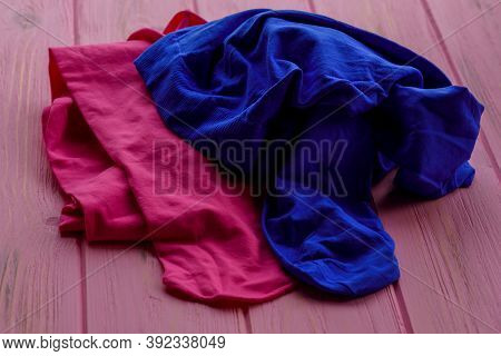 Pink And Blue Tights On Wood Background. Pink Tights As A Female Element Of Clothing. Clothes