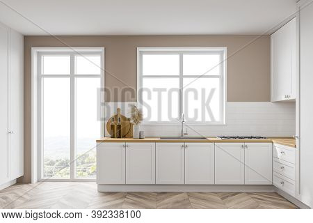 Interior Of Modern Kitchen With Beige And White Walls, Wooden Floor And White Cupboards With Built I