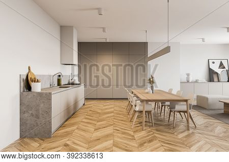 Interior Of Modern Kitchen With White Walls, Wooden Floor, Long Dining Table And Gray Cupboards. 3d