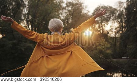 Young Caucasian Fashionable Woman Walking In The Park And Outstretching Hands Near The Lake. High Qu