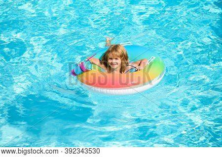 Kid With Colorful Floating Ring. Child In Swimming Pool. Summer Holiday. Kids Water Toys. Little Boy