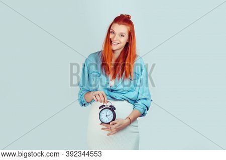 Happy Woman Smiling Holding A Clock At Big Pregnant Belly Showing That Her Biological Watch Is Ticki