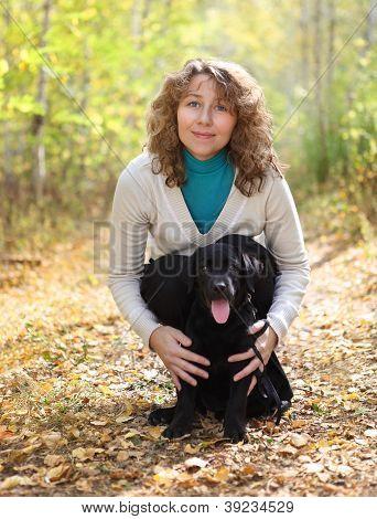 Young Woman With Black Labrador Retriever Puppy