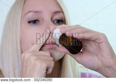 A Woman With A Runny Nose Holds A Medicine In Her Hand, Nasal Spray Irrigations To Stop Allergic Rhi